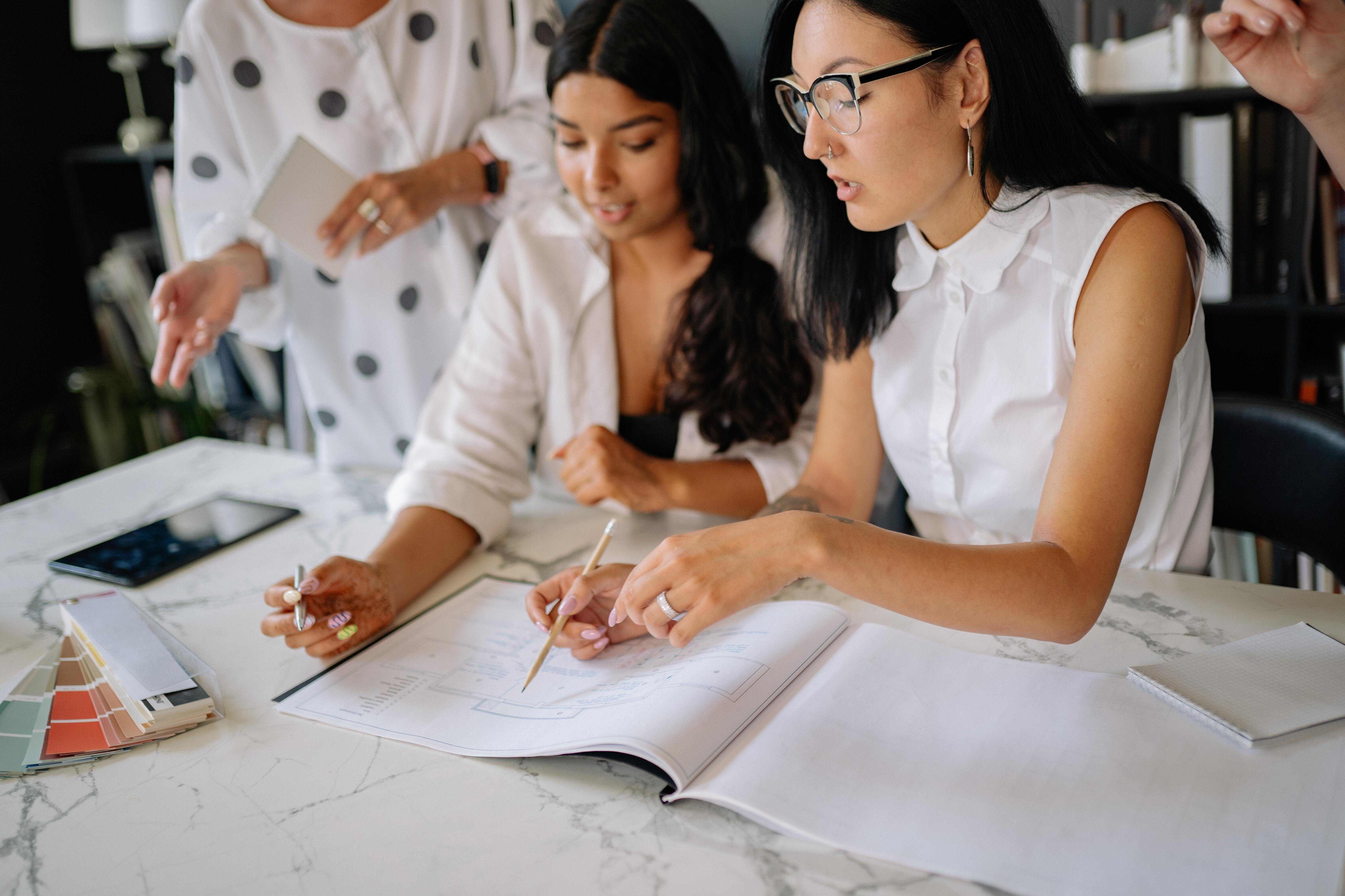 Female coworkers talk over designs and paint samples, each wearing a white blouse.
