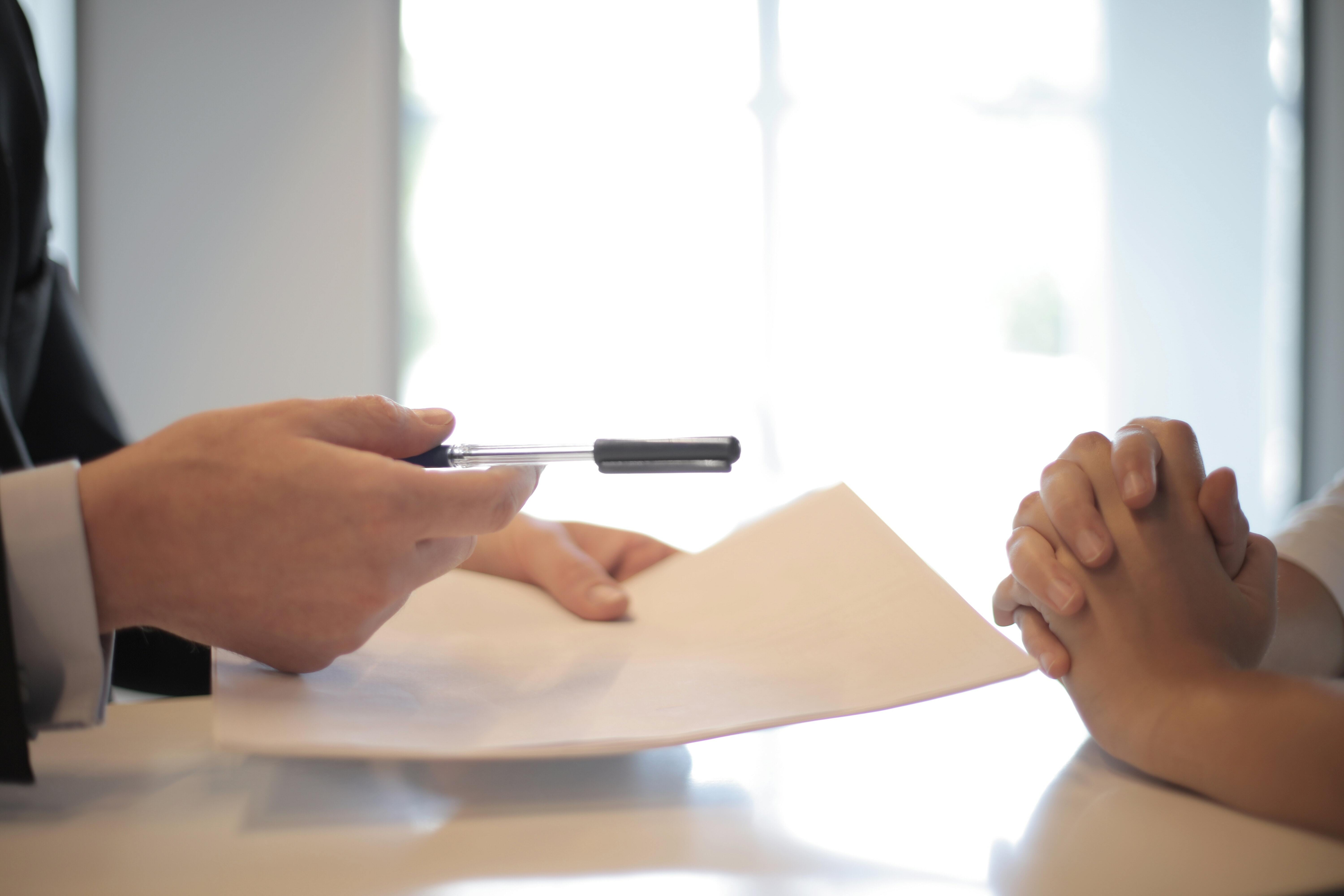 Two people's hands are pictured, sitting on either side of a table, with one person handing the other forms and a pen.
