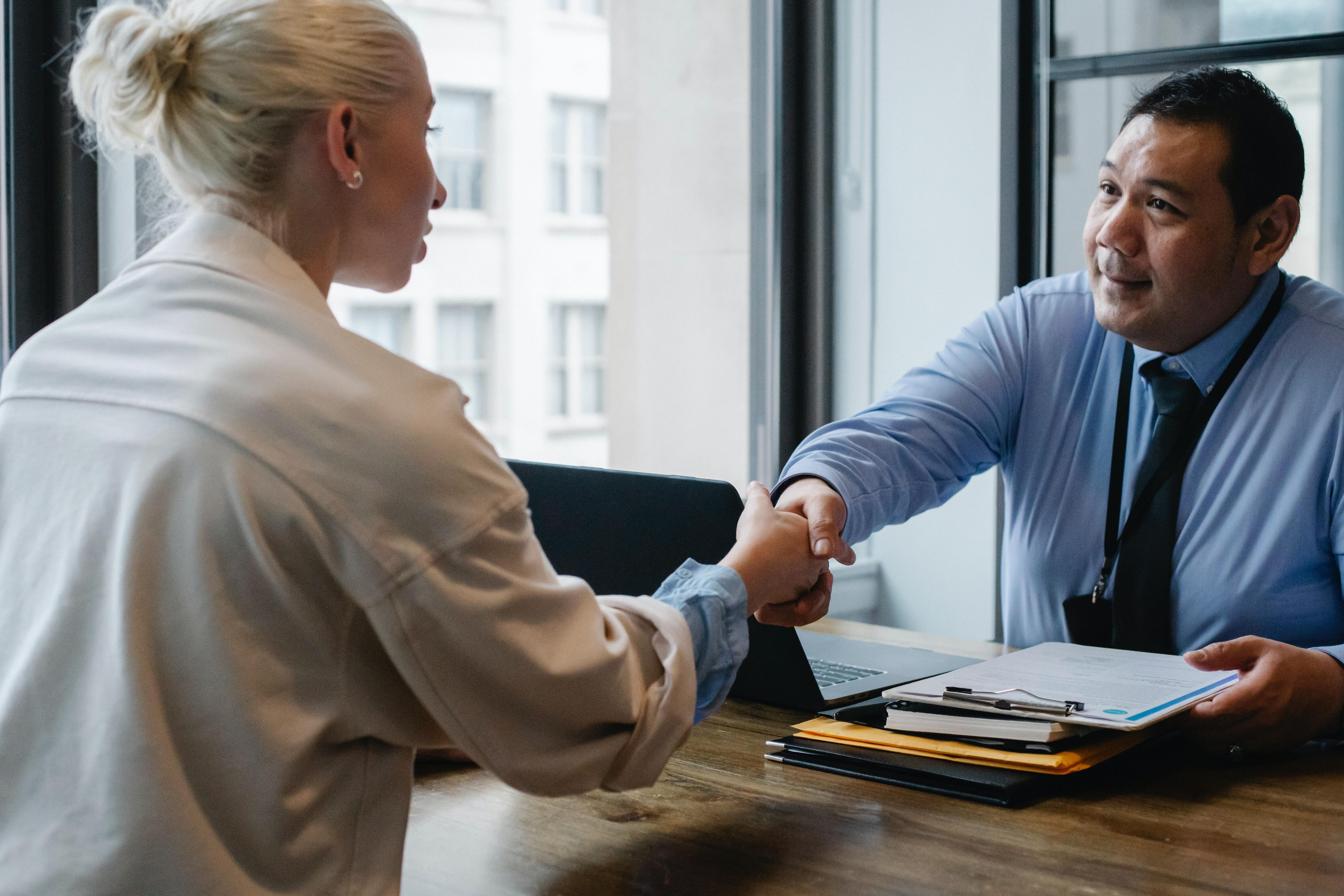 A person wearing a blue button-down and a person wearing a white shirt are shaking hands over a table.