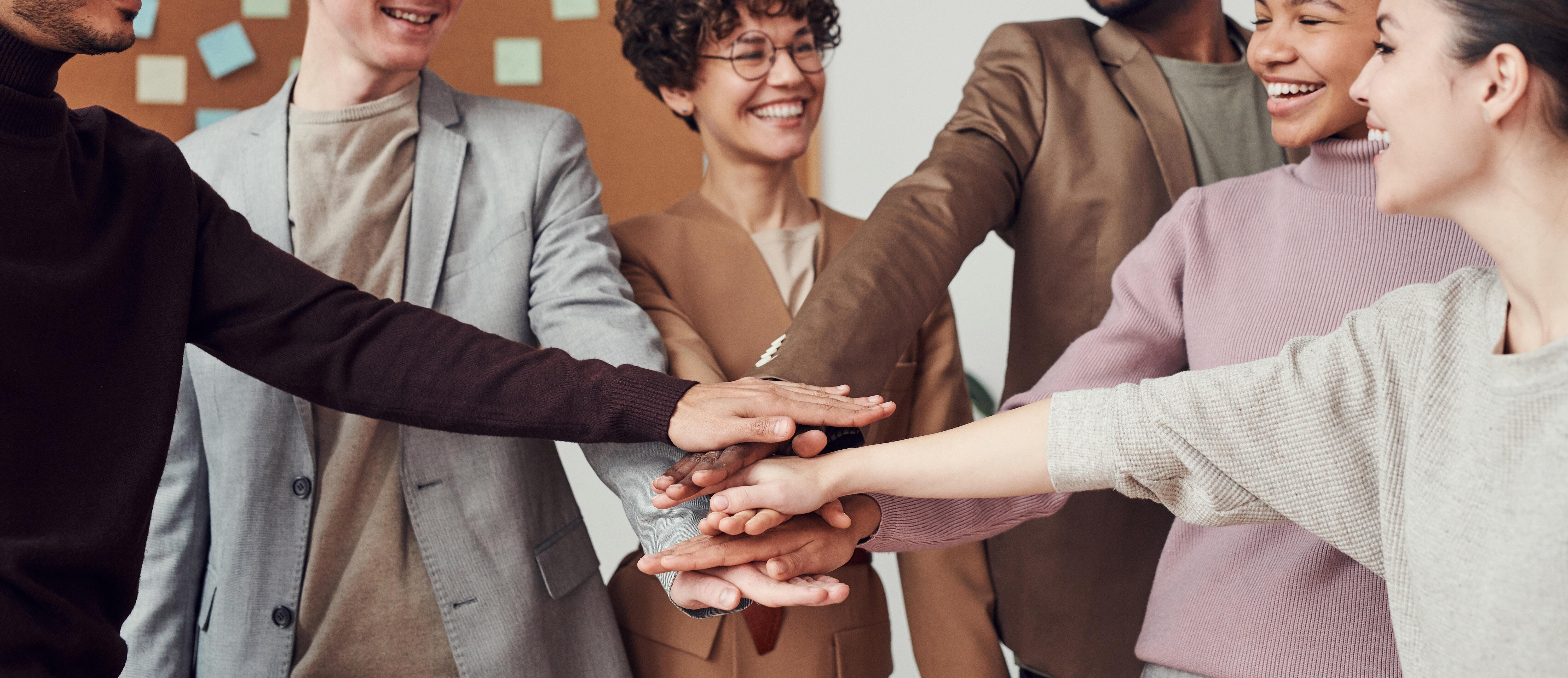Group of co-workers smiling and putting their hands together, creating a team-like environment.
